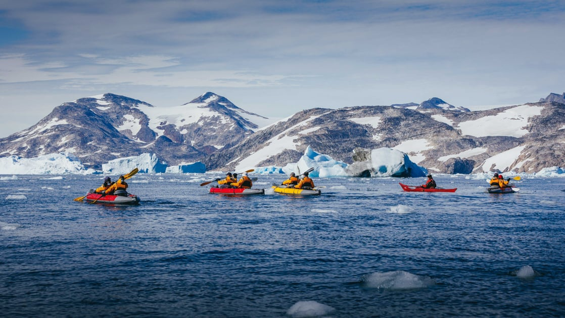 5 tandem paddlers travel on icy blue waters with snowy mountains in the background during The Northwest Passage Canadian High Arctic voyage.