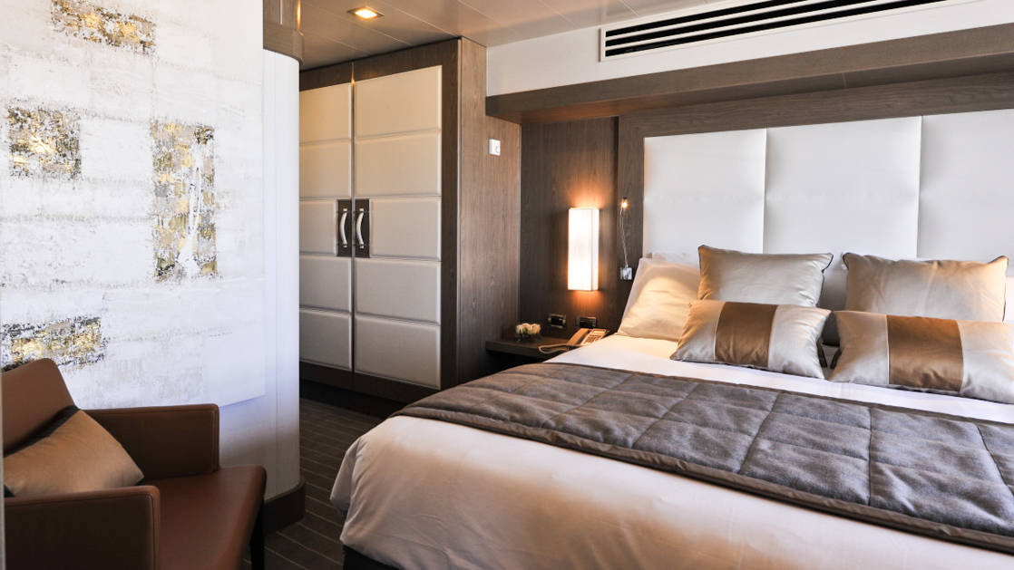 owners suite aboard Le Boreal luxury expedition ship, white leather headboard a closet and a seating area
