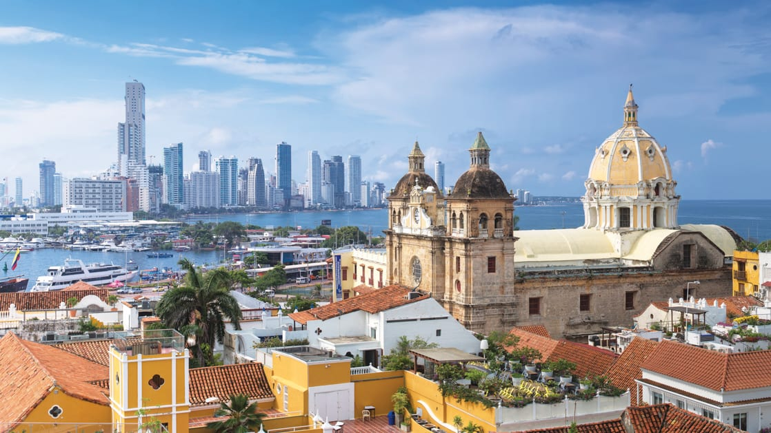 Aerial view of Cartagena, Colombia, with modern high-rise buildings and colorful Caribbean buildings including a church.