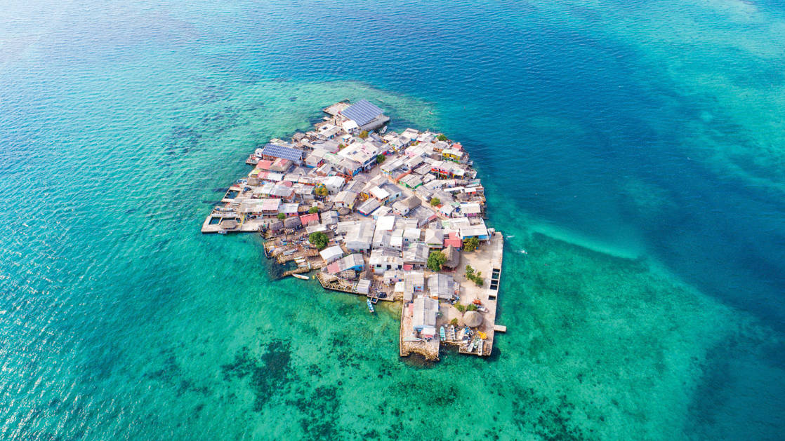 Aerial view of Santa Cruz del Islote, Colombia, a small island packed with buildings & surrounded by turquoise reef and brilliant blue waters.