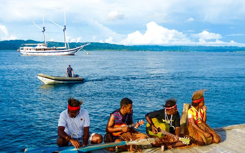 a group of Indonesian musicians sit on a dock in front of the ocean playing instruments, behind them floating in the water is an all white wooden small ship