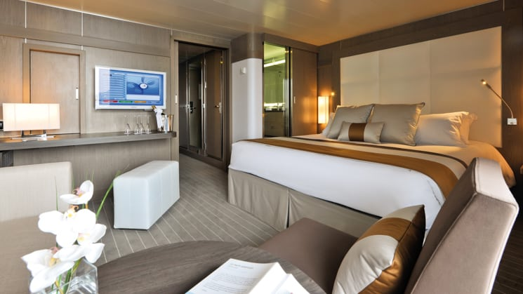 Deluxe Suite aboard L'Austral expedition ship, showing king bed, table, TV, chair & white-&-copper appointments.