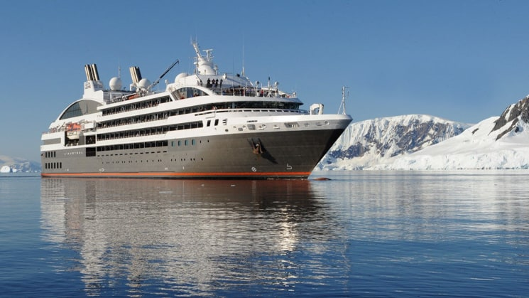 Exterior of expedition ship L'Austral with 6 passenger decks & gray hull, cruising in Antarctica.