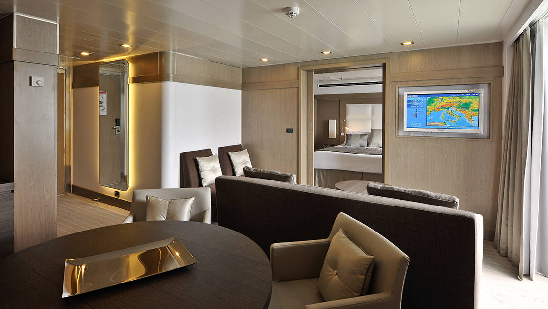 Owner's Suite aboard L'Austral french luxury ship, showing separate living room with couch, TV, table & chairs with view into bedroom.