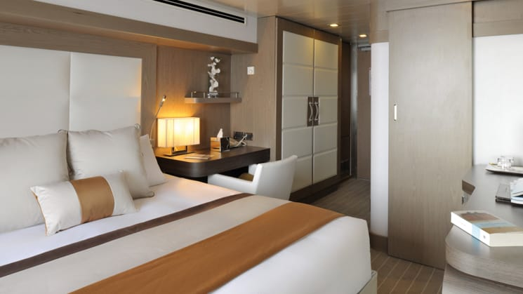Prestige stateroom aboard L'Austral expedition ship, showing king bed, desk & white-&-copper appointments.