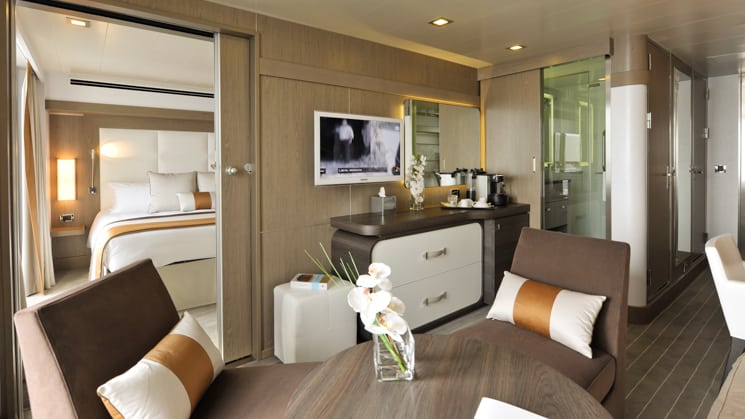 Prestige Suite for Decks 4, 5 & 6 aboard L'Austral expedition ship, showing king bed, table, TV, chairs & white-&-copper appointments.