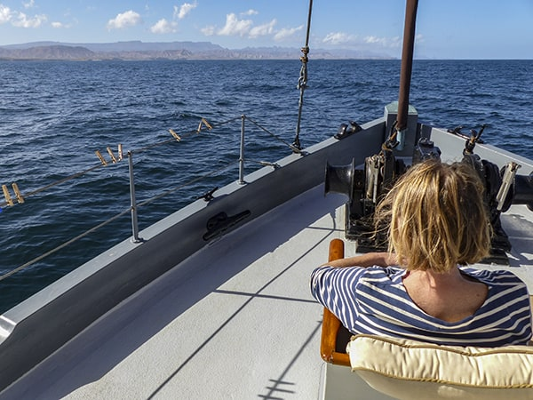 A single female traveler sits on the bow of a small ship in Baja