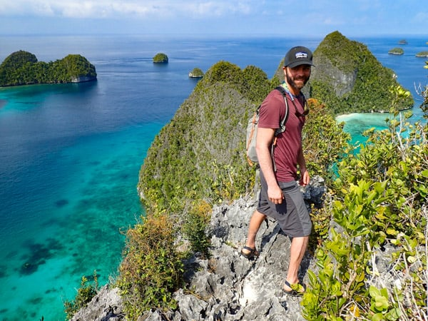 A male traveler stands at the very top of small island structures in Indonesia, blue sky day matches the teal waters, little green islands pop out of the water, seen as part of a small ship Indonesia cruise