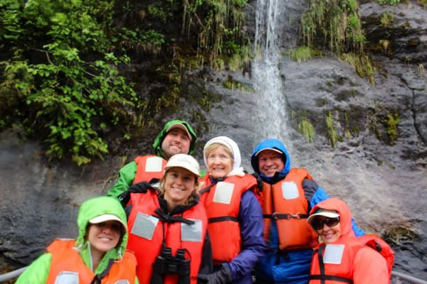 A family of 6 sit on a Kodiak infront of a waterfall, alll wearing orange life vests, as part of a daily activity abord an Alaska small ship cruise