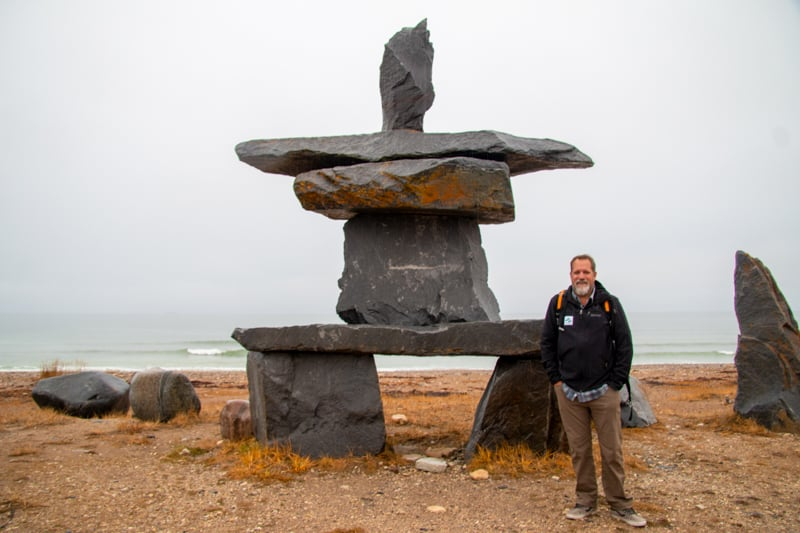 Todd Smith, AdventureSmith Explorations founder, stands in front of a large scale rock formation, also known as a cairn is a man-made pile of stones. The fall colors line the floor, yellow and orange, against the sea shore, on a foggy day.