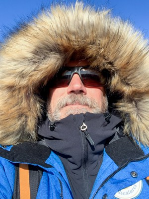 A portrait of Todd Smith founder of AdventureSmith Explorations on the Classic Polar Bear Adventure tour, he is wearing a royal blue jacket with a hood up around his head covered in fur