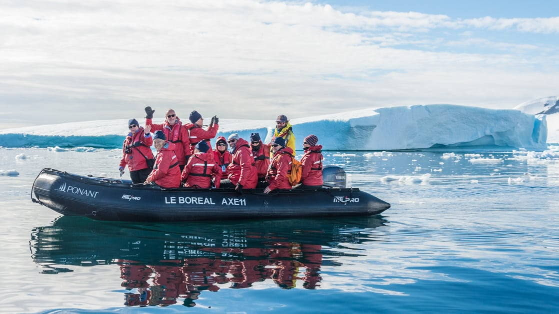 A group of polar travelers in red jackets waves from a Zodiac cruising calm waters on a sunny day in Antarctica during the Emblematic Antarctica voyage.