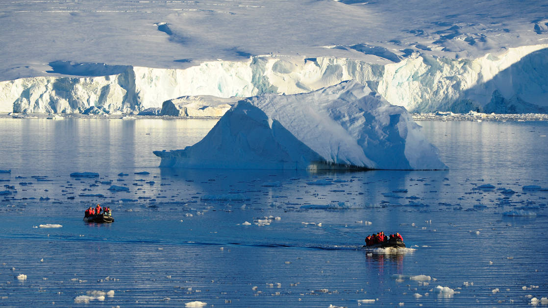 2 Zodiacs cruise past a large iceberg with a massive ice shelf in the background on the Emblematic Antarctica voyage.