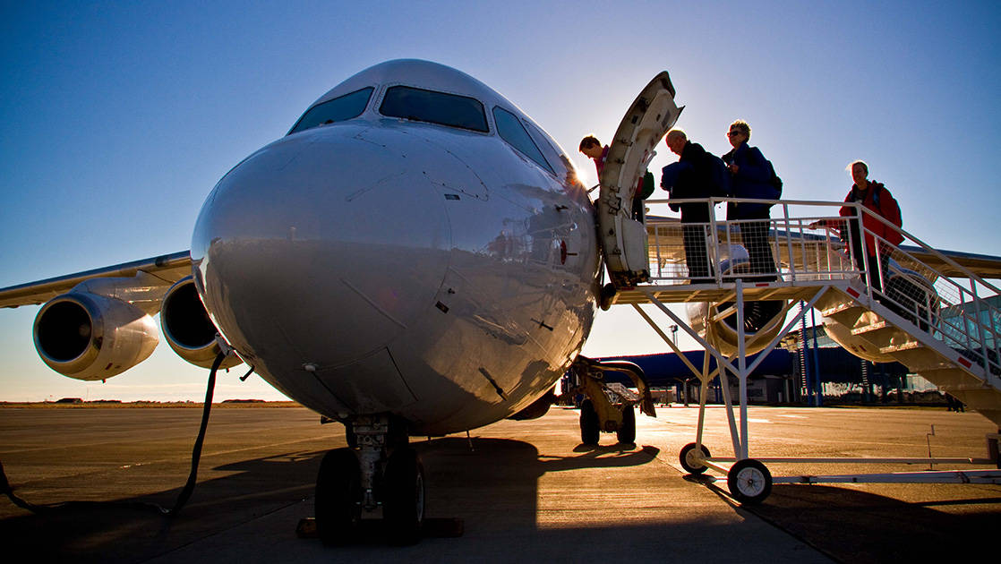 Guests board a plane from the tarmac to start the Falkland Islands Air Cruise.