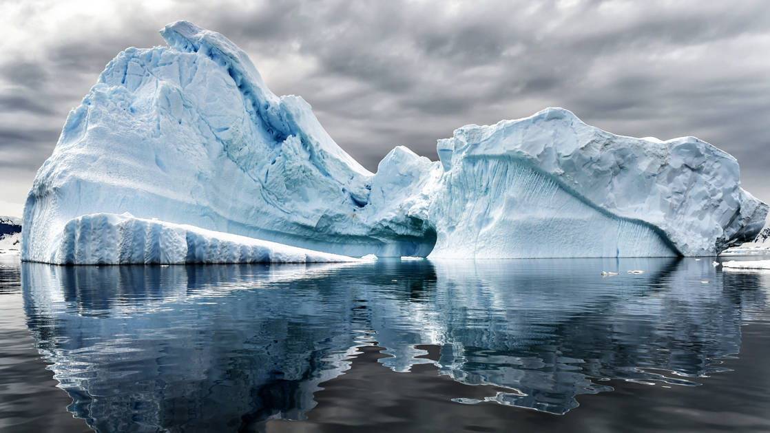 A pair of large icebergs reflect icy blue into glassy waters during the Great Austral Loop luxury Antarctica voyage.