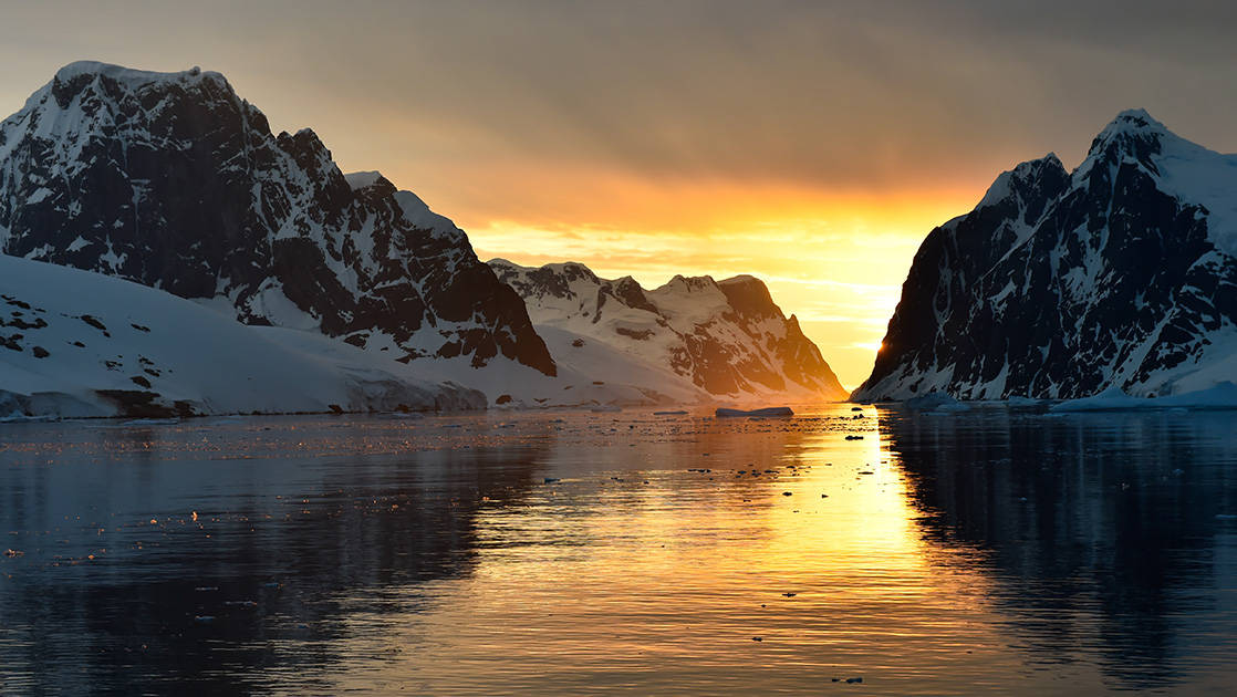 The Lemaire Channel with glassy waters at sunset, flanked by 2 snow-covered mountain ranges. seen during the Great Austral Loop luxury Antarctica voyage.