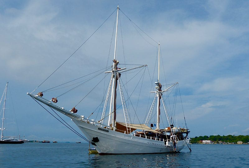 the all white indonesia small ship katharina floats in the ocean, its long wooden bow reaches out