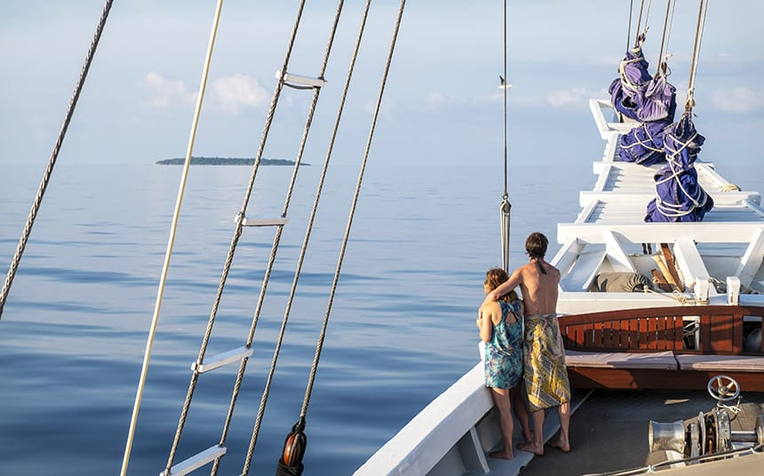 A couple embraces as they look towards the ocean horizon from the bow of a traditional Indonesian small ship. The sky matches the water in its blue hue almost to where you cannot tell where one ends and the other begins except for a single green island splitting the two.