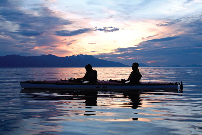 a couple sitting in a kayak is silhouetted against a pink, purple, yellow, and blue sunset on a alaska small ship cruise.