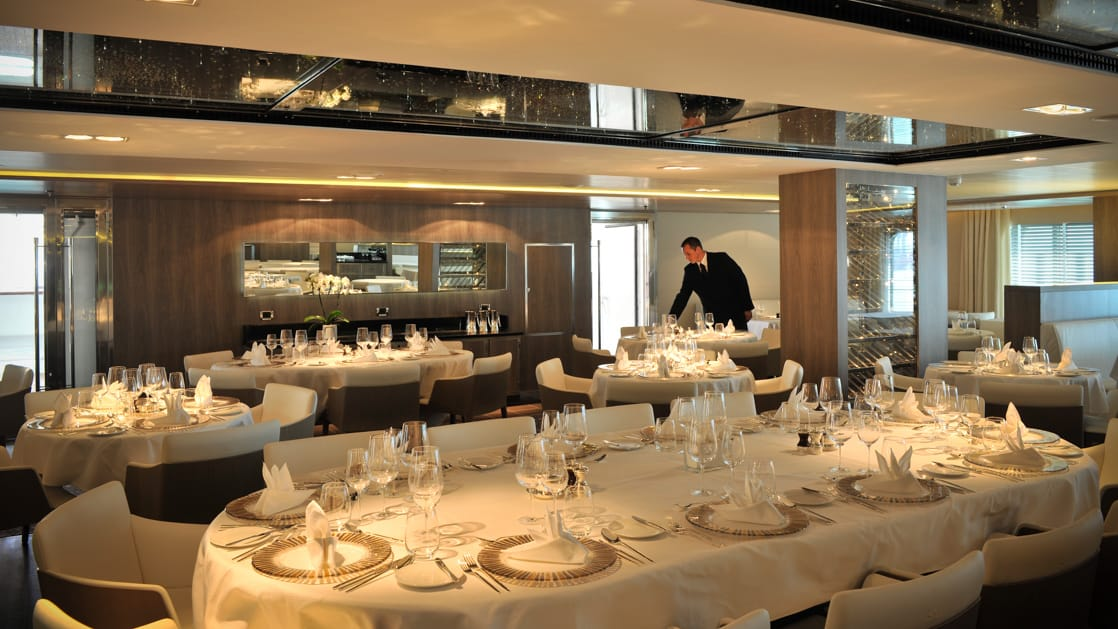 Gastronomic restaurant aboard Le Boreal white linens cover the tables with plate settings and a man in a suit pouring water