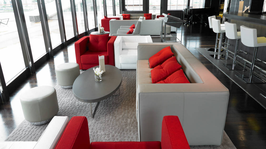 lounge seating aboard Le Boreal, grey couches with red pillows, red arm chairs and coffee tables in front of tall glass wrap around windows