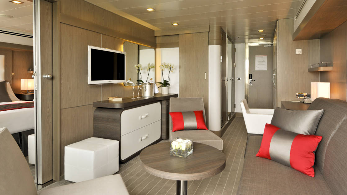 Prestige Suite for Decks 4, 5 & 6 aboard Le Boreal expedition ship, showing king bed, table, TV, chairs & white-&-copper appointments.