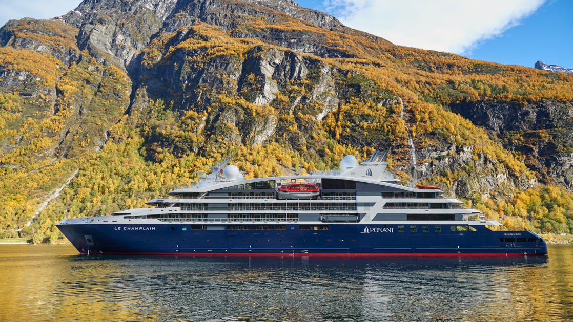 Le Champlain, luxury expedition ship with a red, blue & white exterior, sits in front of cascading waterfalls.
