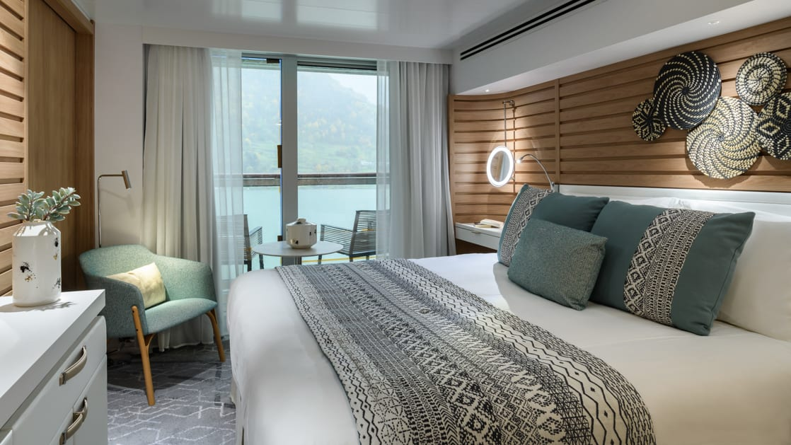 Prestige Suite aboard Le Champlain french small ship, with ethnic chic decor, white linen king bed, private balcony, wooden walls, desk & chair.