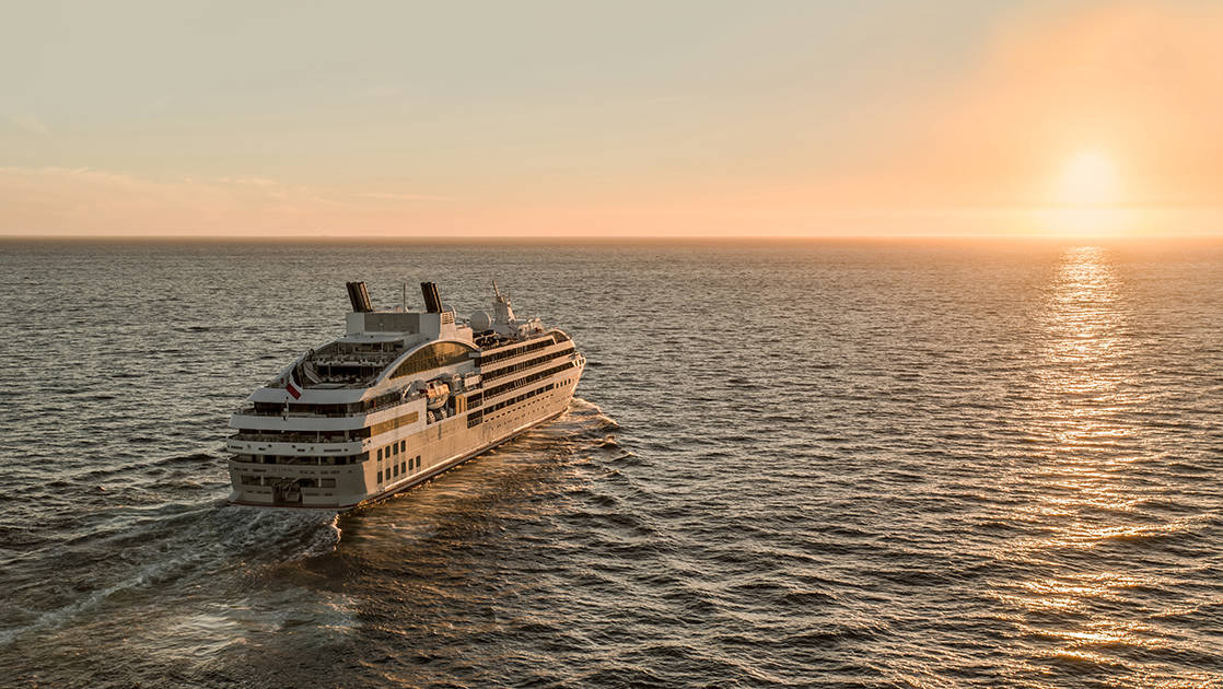 Luxury French ship Le Lyrial cruises toward the sunset, out at sea.