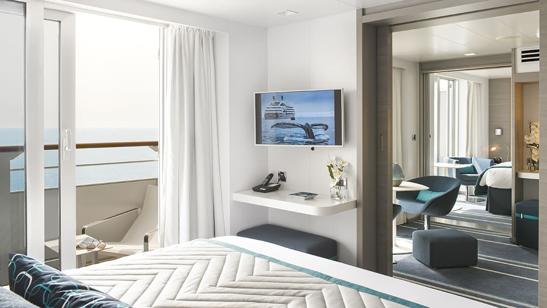 Grand Privilege Suite aboard luxury expedition ship Le Lyrial, in blue-&-white decor with king bed, TV, private balcony, desk, separate living room & second bedroom.