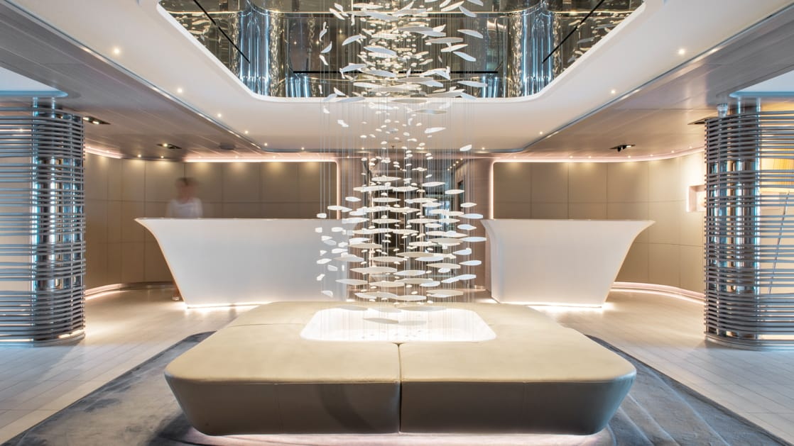 Lobby of Le Lyrial expedition ship, with opulent white desks, round bench, soft lighting & elegant chandelier.
