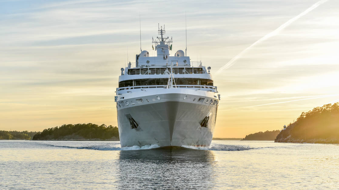 a peach sunrise sky is seen behind a frontal exterior view of the luxury expedition ship Le Soleal, she is mainly white with a light grey hull