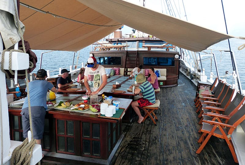 the cruise guests gather around an outdoor but covered dining area on the stern of the ombak putih, some are in line getting food from the buffet line