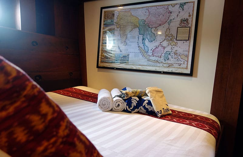a cabin aboard ombok putih a map of indonesia is hung on a white wall, the bed has a white comforter with red pillows, towels and a bag of gifts sits on the bed