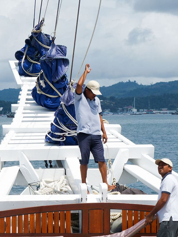 a deck hand oaboard the ombak putih stands on the bow of the white wodden ship holding a rope to the sails