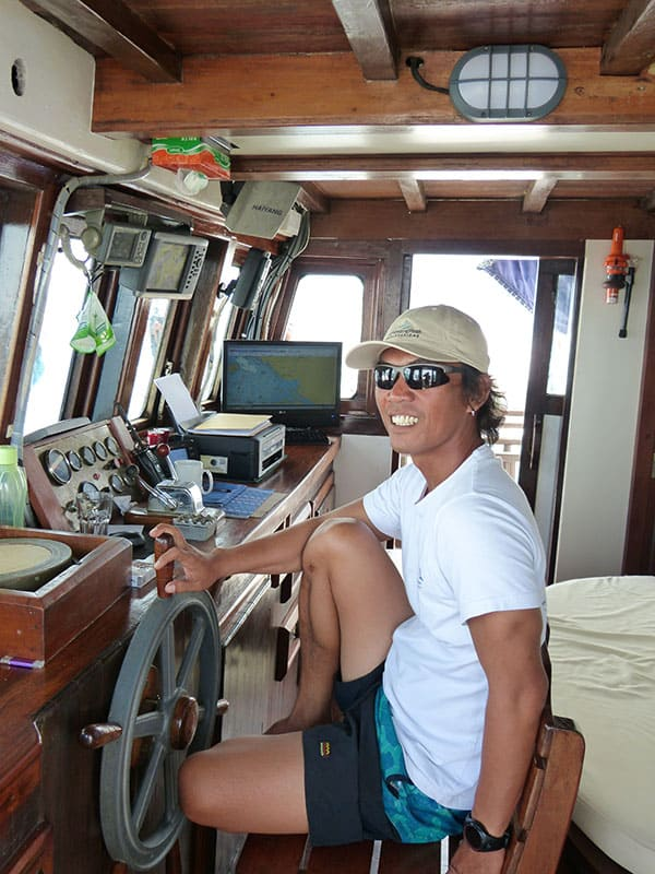 the captain of the small indonesia ship the ombak putih sits in his chair at the wheel of the ship inside the bridge