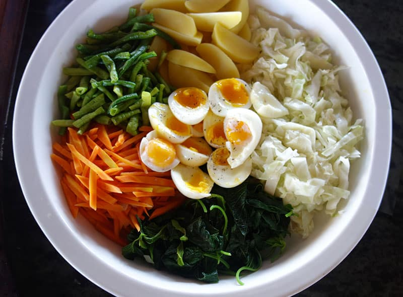 a bowl of indonesia soup, carrots, eggs, green onions, sprouts and broth are inside