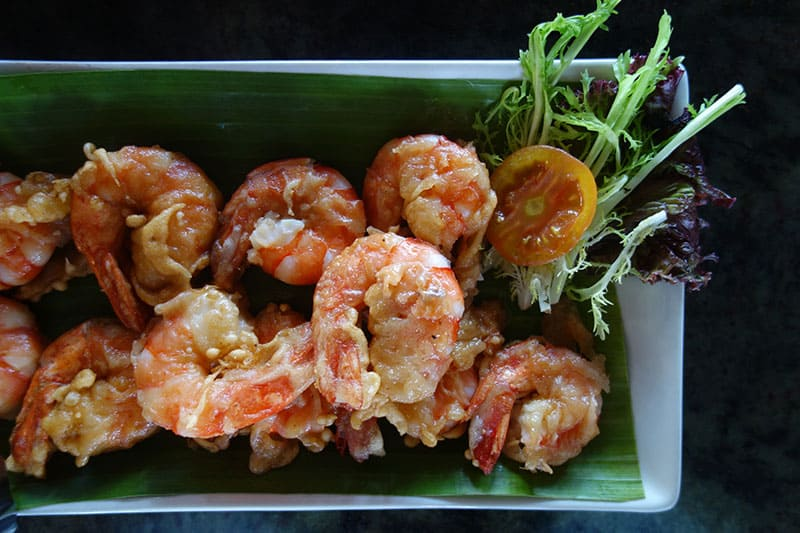 a plate of fried shrimp with a small salad of greens and tomato