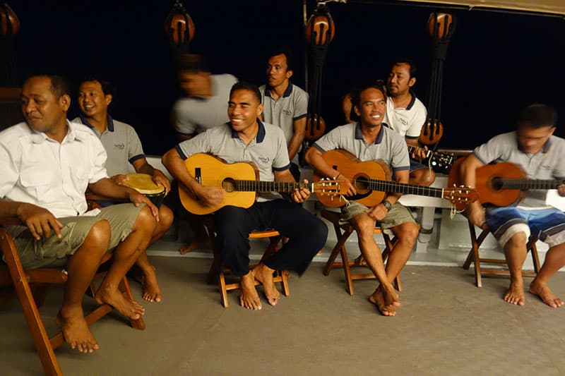 Under the dark sky a group of indonesian crew members sit with guitars and other instruments playing a song aboard a small ship cruise