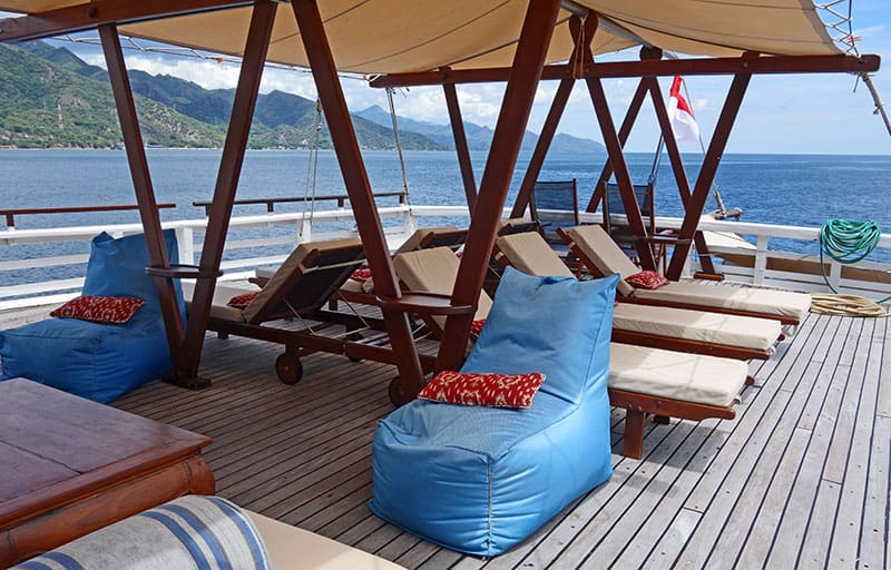 louge area outside on the sterns of the indonesia small ship ombak putih, traditional Indonesian pillow chairs are also set about the deck
