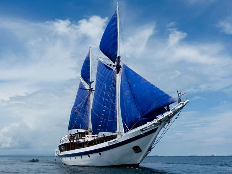 indonesia cruise small ship ombak putih, front view with blue sails up against blue ocean and blue sky