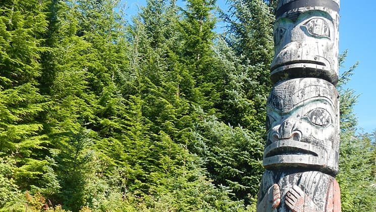 Totem pole on a sunny day beside thick green forest reveals indigenous culture on the Remote Alaska Adventure small ship cruise.