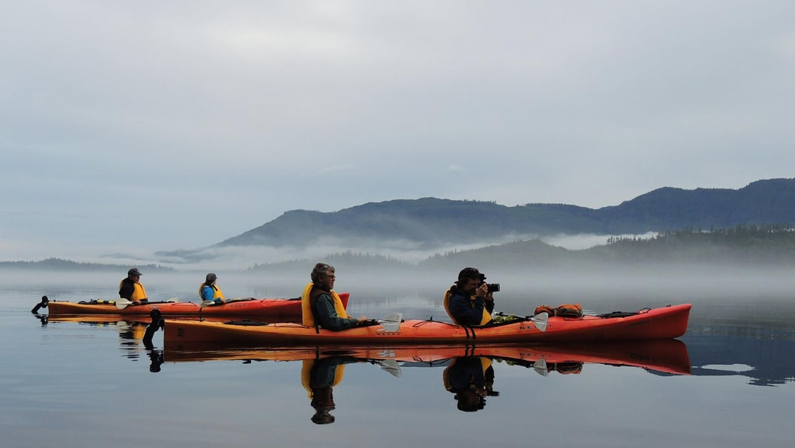 In front of a foggy Alaska mountain range 4 guests wearing life jackets float inside 2 double kayaks and take photos with their camera.