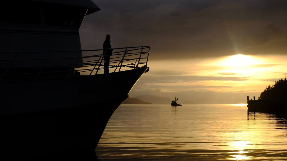 Silhouetted by the setting sun a passenger stands on the bow of a small ship looking at the Alaska landscape yellow with the suns glow.