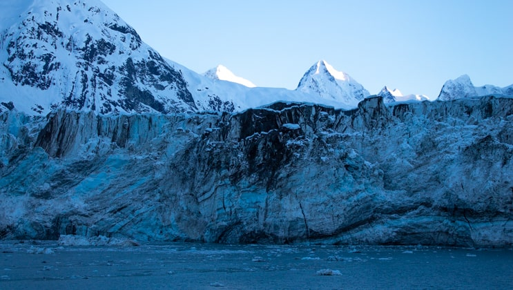 Margerie Glacier with blue ice, black spots & snow-covered mountains in the background on a clear day at sunrise in Glacier Bay National Park.