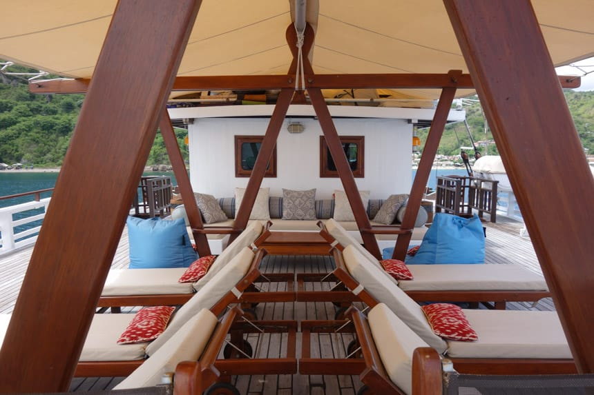 teak beams cross from the ceiling of a overhand to the floor, underneath are lounge chairs with blue and orange pillows