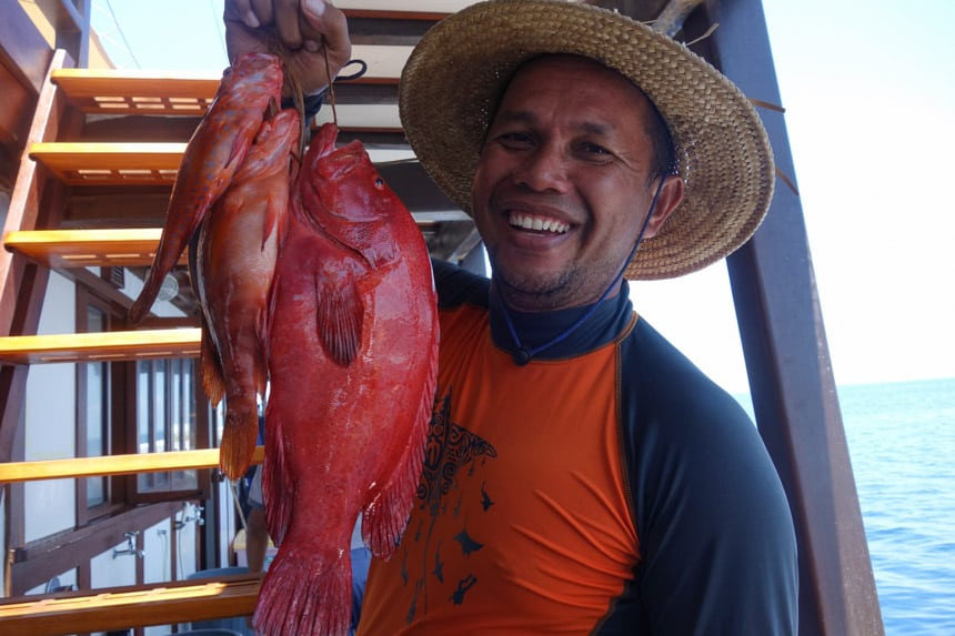 an Indonesian guide aboard the ombak putih ship wears a straw hat with a wide brim, he holds a rope with three red fish on the end that he caught for dinner
