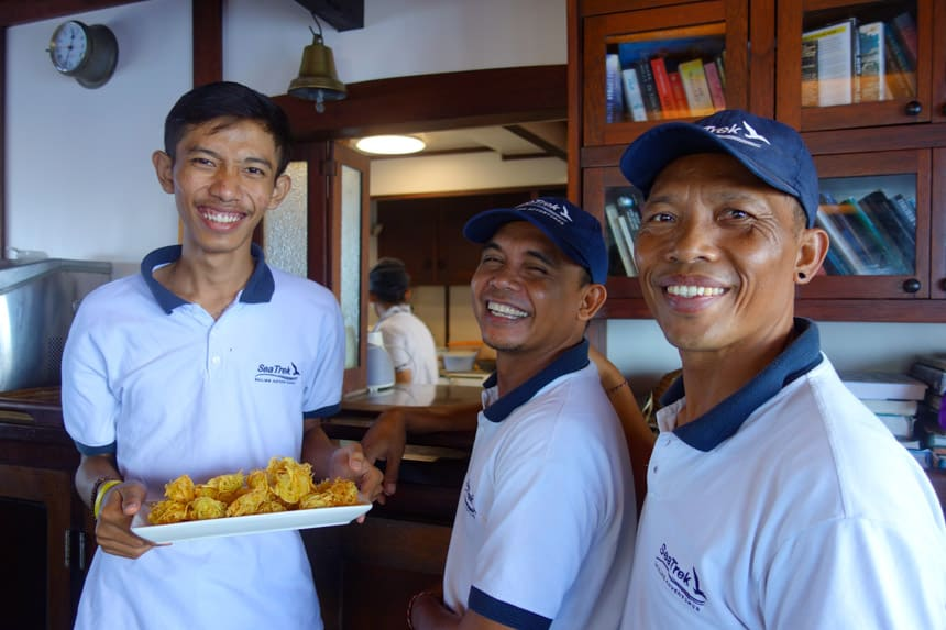 Three Indonesian ship crew members smile for the camera in their uniforms, one is holding a tray of food