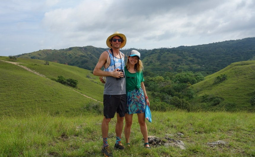 a couple hug and pose for a photo in the green lush mountains of Indonesia, a shore excursion on their remote Sulawesi cruise