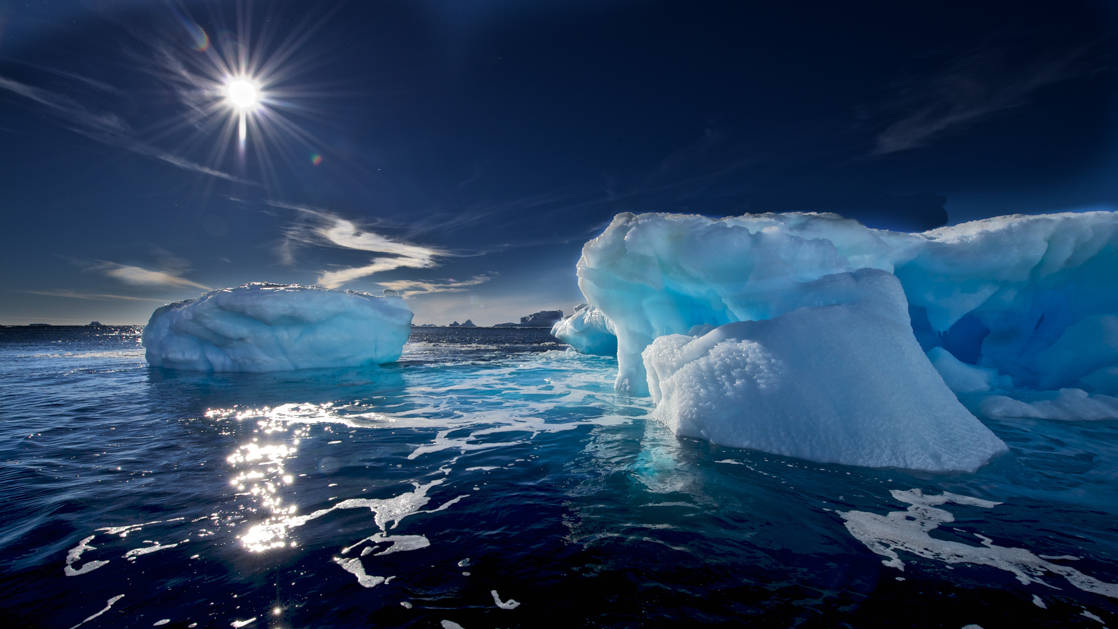 Dark waters & bright blue icebergs float under a bight sun during the Spectacular Ross Sea: West Antarctica Cruise.